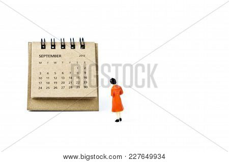 September. Two Thousand Eighteen Year Calendar And Miniature Plastic Woman On White Background.