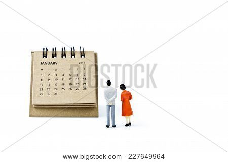 January. Two Thousand Eighteen Year Calendar And Two Miniature Plastic Figures. Man And Woman On Whi