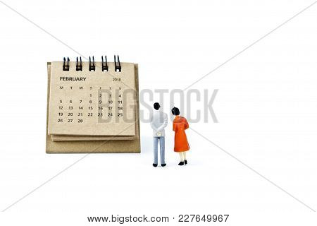 February. Two Thousand Eighteen Year Calendar And Two Miniature Plastic Figures. Man And Woman On Wh