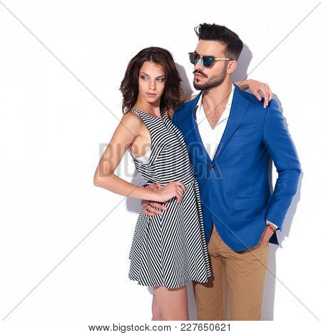 side view of an embraced modern couple looking to side on white studio background