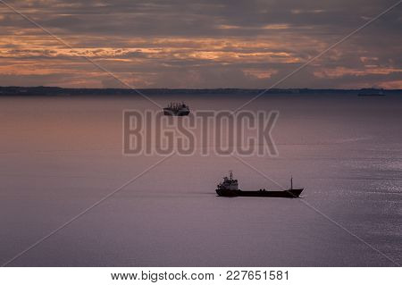 Seascape With Ships At Sunset With Cloudy Sky.