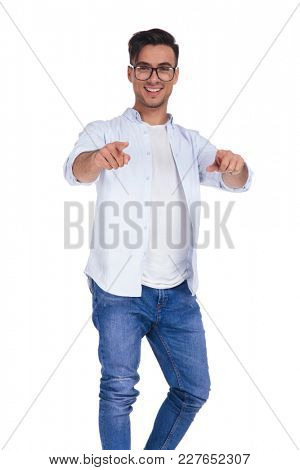 happy young casual man pointing his fingers to the camera on white background