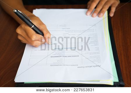 Close-up Of Hand Of Businesswoman Holding Fountain Pen And Filling In Business Information In Applic