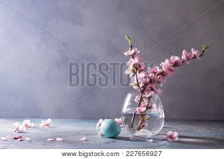 Easter Egg And Pink Cherry Blossom Twigs Posy In Glass Vase On Gray Background With Copy Space
