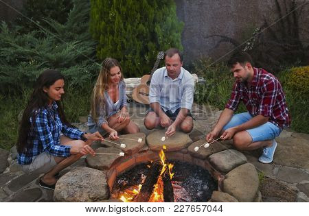 Company Of Young People Holding Sticks With Marshmallows Above Campfire In The Evening. Holiday And