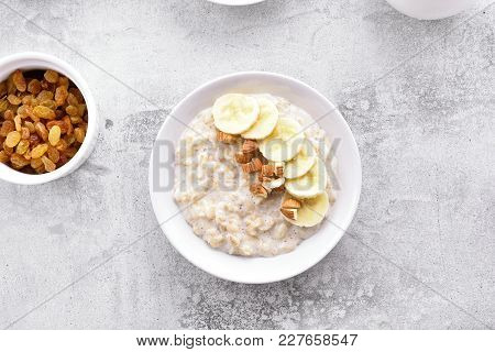 Oats Porridge With Banana Slices And Nuts In Bowl Over Stone Background. Dish For Breakfast. Diet He