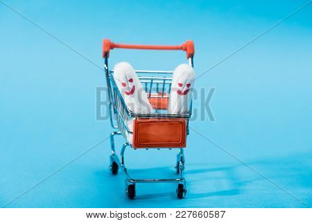 Two Menstrual Tampons With Happy Smileys In Small Shopping Cart On Blue