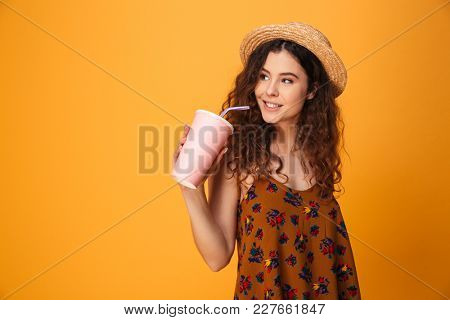 Image of cute young woman standing isolated over yellow background. Looking aside drinking aerated sweet water.