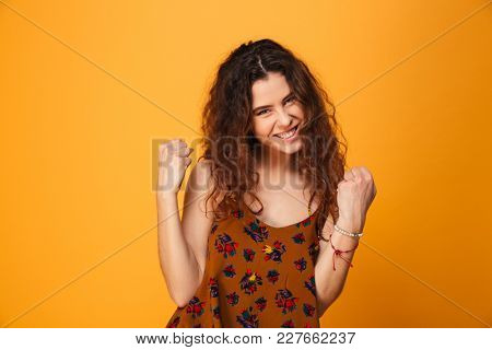 Portrait of a satisfied curly haired girl celebrating success isolated over yellow background