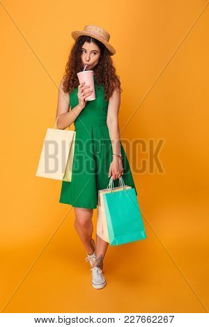 Image of young woman standing isolated over yellow background. Looking aside drinking aerated water holding shopping bags.