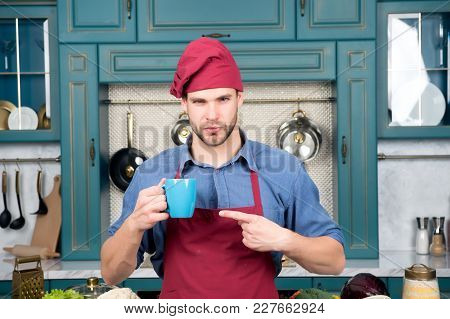 Guy In Red Chef Hat, Apron Point Finger At Blue Cup In Kitchen. Tea Or Coffee Time. Food, Drink, Bev