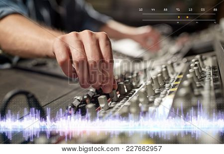 music, technology, people and equipment concept - hands using mixing console in sound recording studio