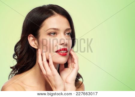 beauty, make up and people concept - happy smiling young woman with red lipstick over green background touching her face