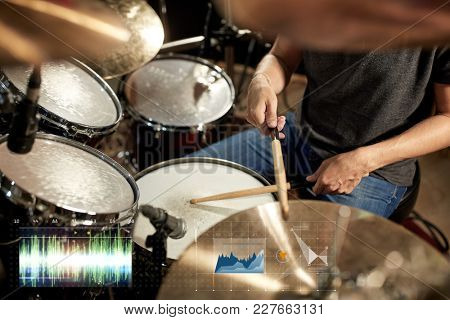 music, people, musical instruments and technology concept - male musician playing drum kit at concert or studio