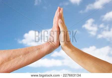 people, age, support and connection concept - close up of senior woman and young woman hands touch over blue sky and clouds background