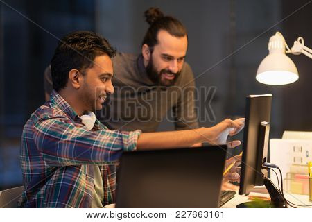 deadline, technology and people concept - creative team with computers working together late at night office