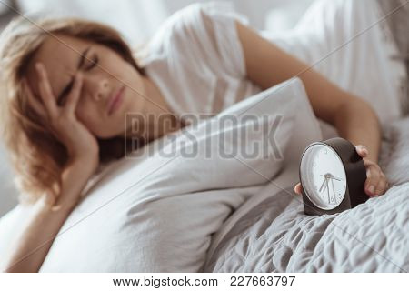 I Need More Sleep. Selective Focus On A Hand Of A Tired Young Lady Grimacing While Holding Her Alarm