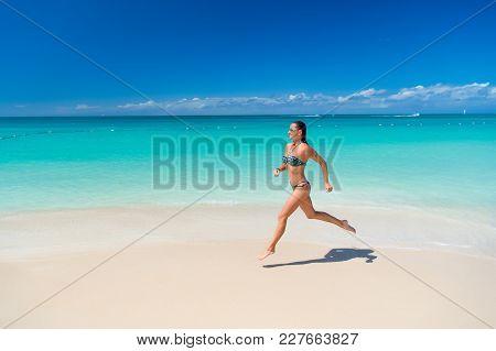 Girl Or Woman In Sexy Bikini Run On Tropical Beach With White Sand, Turquoise Sea Or Ocean Water On
