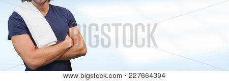 Portrait of a smiling handsome trainer with arms crossed standing in the gym