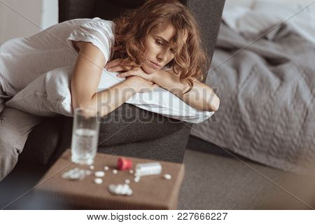Suicidal Thoughts. Depressed Woman Sitting On A Sofa And Thinking About Her Life While Looking At Pi