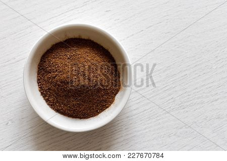 Ground Cloves In White Ceramic Bowl Isolated On White Wood Background From Above.