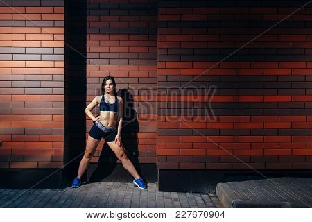 Beautiful Sports Girl Posing Against A Brick Wall Background