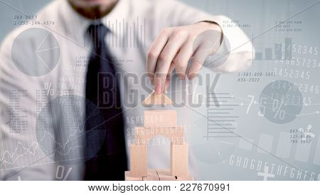 Young handsome businessman using wooden building blocks with data and numbers around him