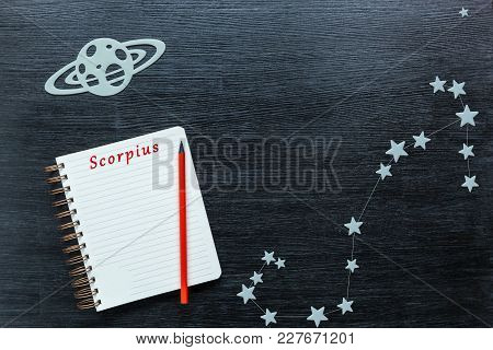 Zodiacal Star, Constellations Scorpius On A Black Background With A Notepad And Pencil.