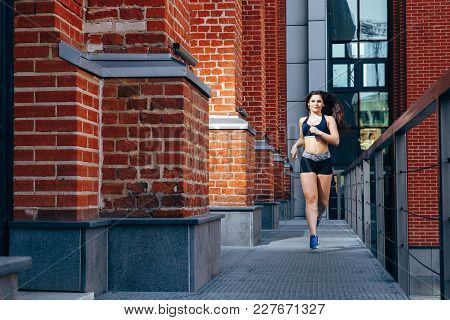 Woman Running At Outdoor On A Background Of Cityscape.