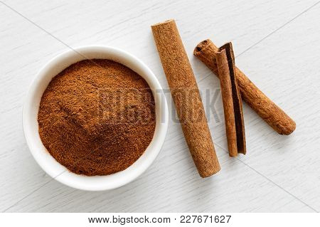 Finely Ground Cinnamon In White Ceramic Bowl Isolated On White Wood Background From Above. Cinnamon