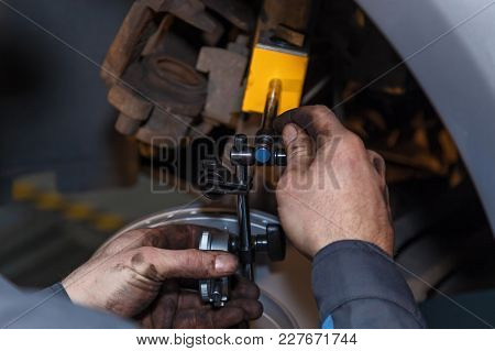 The Man Is Repairing The Disc Brake Machine, Close-up. Disk Brake Repair In The Car.
