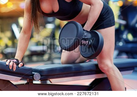 sport, fitness, bodybuilding, weightlifting and people concept - close up of young woman with dumbbell flexing muscles in gym from back