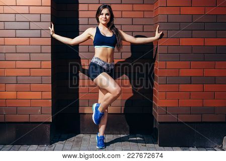 Beautiful Fitness Model Posing Against A Brick Wall Background