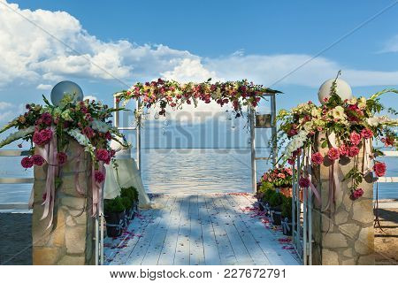 Beautiful Wedding On The Beach. View Of The Sea. The Wedding Place Is Decorated With Bouquets Of Flo