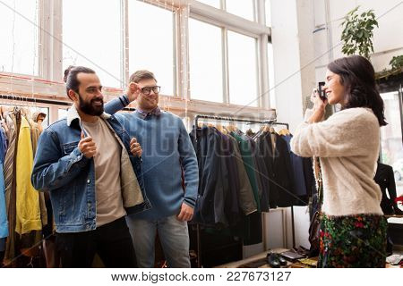 sale, shopping, fashion and people concept - friends choosing clothes and photographing by film camera at vintage clothing store