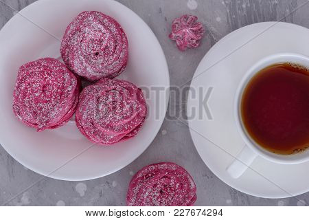Meringues On Plate And Cup Hot Tea On Gray Background