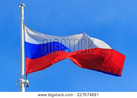 Flag Of Russian Federation On The Blue Sky Background. Waving Flag Of Russia