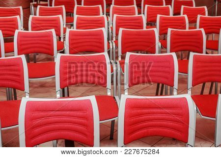 A Large Concert Hall Full Of Emty Red Seats
