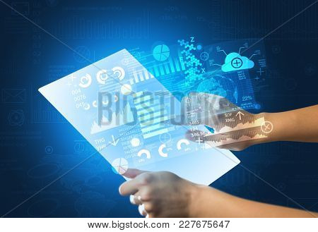 Young female hand holding a tablet with blue graphs