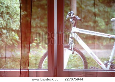 A Mountain Bike Stands Behind The Curtains Of A Window.