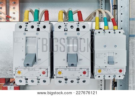 Power Circuit Breakers Are Arranged In A Row In An Electric Cabinet. Cables Or Marked Wires Are Conn