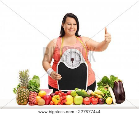 Overweight woman with a weight scale making a thumb up gesture behind a table with fruit and vegetables isolated on white background