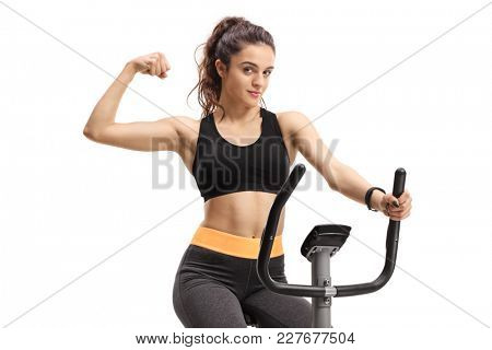 Teenage girl exercising on a cross-trainer machine and flexing her biceps isolated on white background
