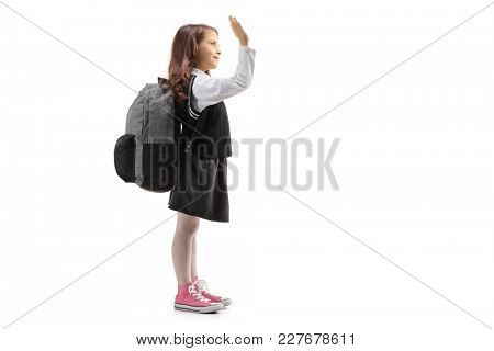 Full length profile shot of a little schoolgirl making a high-five gesture isolated on white background