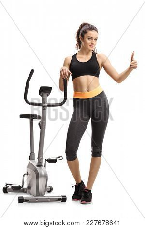 Full length portrait of a teenage girl leaning on a cross-trainer machine and making a thumb up gesture isolated on white background
