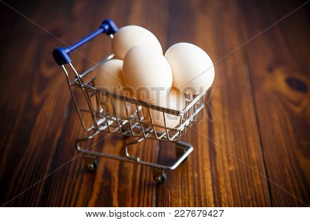 Shopping Cart Full With Eggs On A Wooden Table