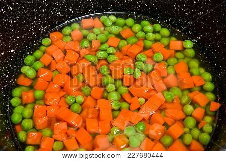 Frozen Peas And Carrots In The Pan With Water, Vegetables And Frozen Foods