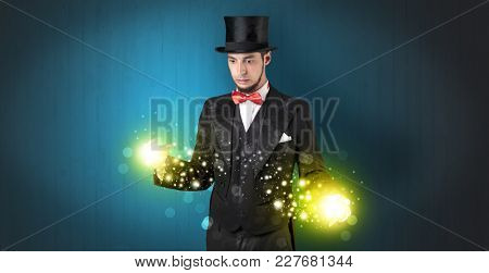 Handsome illusionist holding his superpower on his hands with gold wallpaper