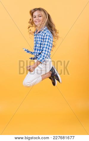 Child Bounce With Smiling Face. Girl Jump On Orange Background. Happy Childhood Concept. Fashion, Be