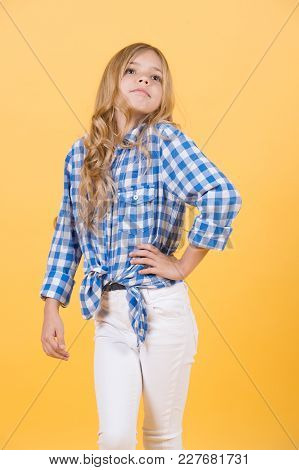 Kid Pose With Long Blond Hair. Girl In Shirt And Pants On Orange Background. Fashion, Beauty, Style.